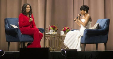 """Former first lady Michelle Obama, left, is interviewed by Phoebe Robinson during the """"Becoming: An Intimate Conversation with Michelle Obama"""" event at the Wells Fargo Center on Thursday, Nov. 29, 2018, in Philadelphia."""