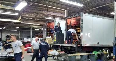 Members of PA Task Force 1 load trucks with supplies ahead of the 630-mile drive from Philly to South Carolina.