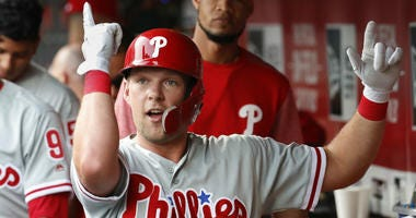 Philadelphia Phillies' Rhys Hoskins celebrates in the dugout after hitting a solo home run off Cincinnati Reds starting pitcher Tyler Mahle during the first inning of a baseball game, Thursday, July 26, 2018, in Cincinnati.
