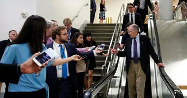 Senate Judiciary Committee Chairman Chuck Grassley, R-Iowa, talks with reporters as he uses the escalator on Capitol Hill, Wednesday, Oct. 3, 2018 in Washington.