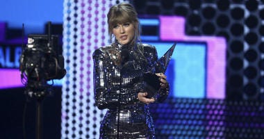 """Taylor Swift accepts the award for favorite pop/rock album for """"Reputation"""" at the American Music Awards on Tuesday, Oct. 9, 2018, at the Microsoft Theater in Los Angeles."""