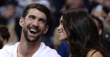 Olympic gold medal swimmer Michael Phelps attends the game between the Phoenix Suns and the Cleveland Cavaliers with his wife Nicole Johnson during the second half at Talking Stick Resort Arena.