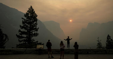 In this July 25, 2018 file photo, Hannah Whyatt poses for a friend's photo as smoke from the Ferguson fire fills Yosemite Valley in Yosemite National Park, Calif.