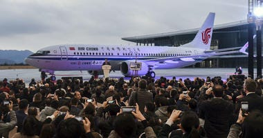 In this Dec. 15, 2018, photo released by Xinhua News Agency, invited guests take photos of the Boeing 737 Max 8 airplane deliver to Air China during a ceremony at Boeing Zhoushan 737 Completion and Delivery Center in Zhoushan, China.