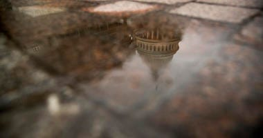 FILE- In this Feb. 22, 2019, file photo the dome of the U.S. Capitol Building is visible in reflection in Washington. On Friday, March 22, the Treasury Department releases federal budget data for February.