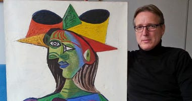 "This image released on Tuesday March 26, 2019 by Arthur Brand, shows Dutch art detective Arthur Brand with ""Buste de Femme"", a recovered Picasso painting. The painting was stolen from a wealthy Saudi's yacht 20 years ago."
