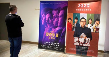 "A customer looks at a movie poster for the film ""Bohemian Rhapsody"" at a movie theater in Beijing, Wednesday, March 27, 2019."