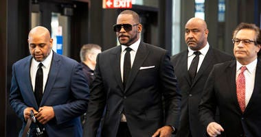 FILE - In this March 22, 2019 file photo, R. Kelly walks with attorneys and supporters into the Leighton Criminal Courthouse in Chicago. Kelly gave a 28-second performance and spent about half an hour more hobnobbing with fans who paid $50 to $100 to see