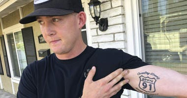 Brendan Kelly speaks with reporters outside his home, as he shows his Route 91 tattoo, Thursday, Nov. 8, 2018, in Thousand Oaks, Calif.