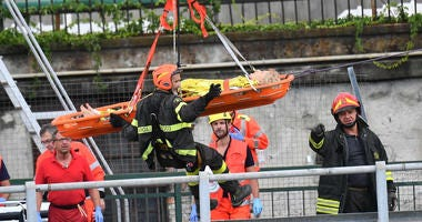 Rescuers recover an injured person after the Morandi highway bridge collapsed in Genoa, northern Italy, Tuesday, Aug. 14, 2018.
