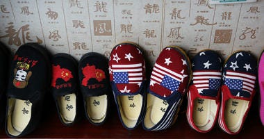 In this July 13, 2018, photo, Chinese-made childrens shoes carrying a Chinese map and U.S. flags are on display for a sale at a shop in Beijing.