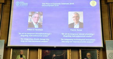 The laureates of the Nobel Prize in Economics displayed on the screen, William Nordhaus, left, and Paul Romer during a press conference at the The Royal Swedish Academy of Sciences in Stockholm, Monday Oct. 8, 2018.