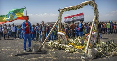 Students from Hama elementary school, who walked an hour and a half from their school in the surrounding area to pay their respects, stand next to floral tributes at the scene where the Ethiopian Airlines Boeing 737 Max 8 crashed