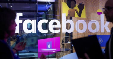 In this April 18, 2017 file photo, conference workers speak in front of a demo booth at Facebook's annual F8 developer conference, in San Jose, Calif.