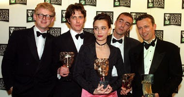 """The cast of """"Four Weddings and a Funeral"""" celebrates its British Academy Film Awards win in 1994 in London.The cast has reunited for a short sequel that will air as part of Red Nose Day on May 23 on NBC."""