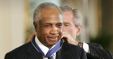 In this Nov. 9, 2005, file photo, President Bush awards baseball legend Frank Robinson the Presidential Medal of Freedom Award in the East Room of the White House in Washington.