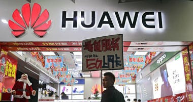 In this Dec. 18, 2018, file photo, a worker holds a sign promoting a sale for Huawei 5G internet services at a mobile phone retail shop in Shenzhen in south China's Guangdong province.