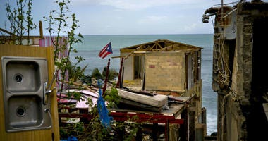 In this Oct. 5, 2017 file photo, a Puerto Rican national flag is mounted on debris of a damaged home in the aftermath of Hurricane Maria in the seaside slum La Perla, San Juan, Puerto Rico.