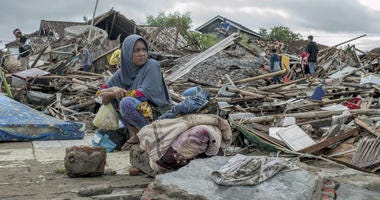 A tsunami survivor sits on a pice of debris as she salvages items from the location of her house in Sumur, Indonesia, Monday, Dec. 24, 2018.
