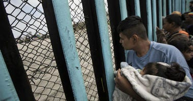 member of the Central American migrant caravan, holding a child, looks through the border wall