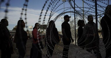 Pedestrians stand near barbed wire at a legal Mexico-U.S. border crossing as they prepare to leave Tijuana, Mexico, Monday, Nov. 19, 2018.