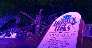 The sign for the Hidden Oaks apartment complex in Jefferson City Missouri stands bent on May 23, 2019, from an apparent tornado in front of a tree that was ripped apart.