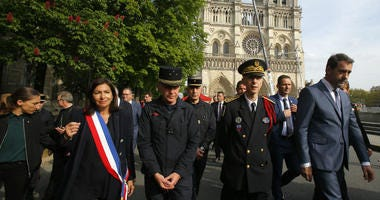 French Interior Minister Christophe Castaner, right, Paris mayor Anne Hidalgo, left, and other officials Paris walk by Notre Dame cathedral Thursday, April 18, 2019 in Paris.