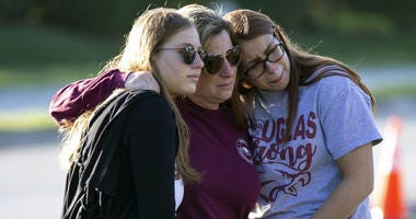 Emma Rothenberg, left to right, with her mother Cheryl Rothenberg and sister, Marjory Stoneman Douglas High School student Sophia Rothenberg embrace at a memorial marking the one-year anniversary of a mass shooting at the school in Parkland, Fla.