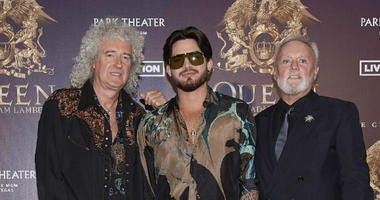 "In this Aug. 28, 2018, file photo, Brian May, from left, Adam Lambert, and Roger Taylor of Queen + Adam Lambert pose for a photo at the ""The Crown Jewels"" residency press conference at the MGM Resorts aviation hanger in Las Vegas."