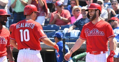 Philadelphia Phillies catcher J.T. Realmuto (10) is greeted by Philadelphia Phillies outfielder Bryce Harper (3) after hitting a home run in the fourth inning of the spring training game against the Toronto Blue Jays at Spectrum Field.