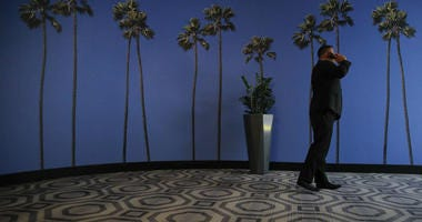 In this May 4, 2018, file photo a man talks on the phone in a hallway adorned with the palm tree-printed wallpaper at a hotel near the Los Angeles International Airport in Los Angeles.