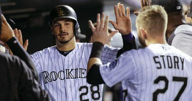 Colorado Rockies' Nolan Arenado (28) is congratulated by teammate Trevor Story (27) after scoring a run against the Philadelphia Phillies during the third inning of a baseball game on Monday, Sept. 24, 2018, in Denver.