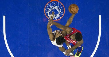 Cleveland Cavaliers' Collin Sexton, left, shoots against Philadelphia 76ers' Joel Embiid, right, of Cameroon, during the first half of an NBA basketball game, Tuesday, March 12, 2019, in Philadelphia.