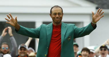 Tiger Woods smiles as he wears his green jacket after winning the Masters golf tournament Sunday, April 14, 2019, in Augusta, Ga.