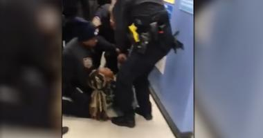 The chaotic, two-minute video shows police wrestling with Jazmine Headley as people scream in the background.