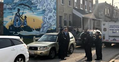 Authorities confer on the scene of a quadruple homicide, where four people were discovered to have been murdered execution style in the basement of a West Philadelphia row home.