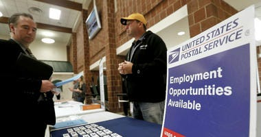 In this Nov. 2, 2017, file photo a recruiter from the postal service, right, speaks with an attendee of a job fair in the cafeteria of Deer Lakes High School in Cheswick, Pa.