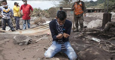 """Bryan Rivera cries after looking at the remains of his house, after his family went missing during the Volcan de Fuego or """"Volcano of Fire"""" eruption, in San Miguel Los Lotes, Guatemala, Thursday, June 7, 2018."""