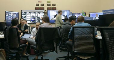 Workers gather and sit and their desks during a demonstration in the war room, where Facebook monitors election related content on the platform, in Menlo Park, Calif., Wednesday, Oct. 17, 2018.