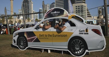 People pose in a cutout taxi cab ahead of the 2019 Eurovision Song Contest in Tel Aviv, Israel, Monday, May 13, 2019.