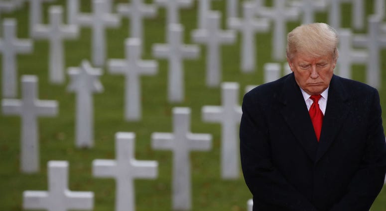 President Donald Trump stands in front of headstones during an American Commemoration Ceremony, Sunday Nov. 11, 2018, at Suresnes American Cemetery near Paris.