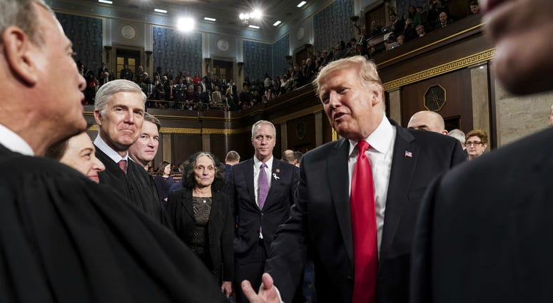President Donald Trump talks to Supreme Court Chief Justice John Roberts while leaving the House chamber after giving his State of the Union address to a joint session of Congress, Tuesday, Feb. 5, 2019 at the Capitol in Washington.