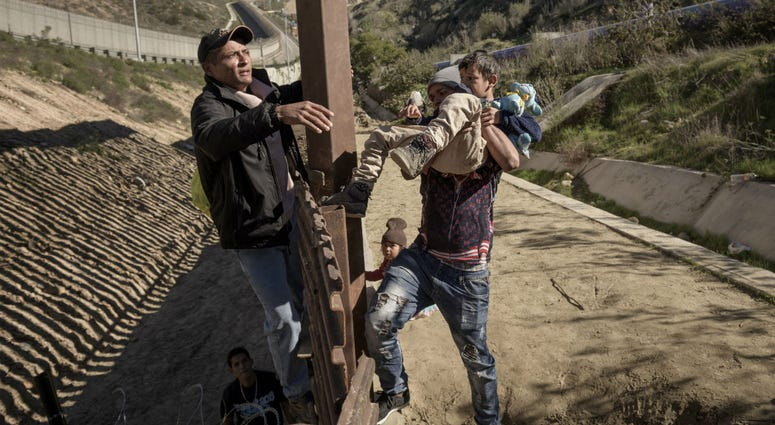 In this Saturday, Dec. 29, 2018, file photo, a man passes a Mexican migrant baby to her mother after they jump the border fence to get to the U.S. side to San Diego, from Tijuana, Mexico.