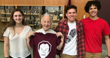 """John """"Woody"""" McGoldrick (second from left) poses with his shirt and students, (from left) senior Becca Gable, freshman Ethan Weilheimer, and senior Josiah Campbell."""