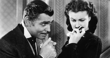 """American actor Clark Gable in his role as Rhett Butler kissing the hand of a tearful Scarlett O'Hara, played by Vivien Leigh, in """"Gone With The Wind."""""""