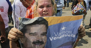 A supporter of Venezuela's President Nicolas Maduro holds a poster of him during a rally in Urena, Venezuela, Monday, Feb. 11, 2019.