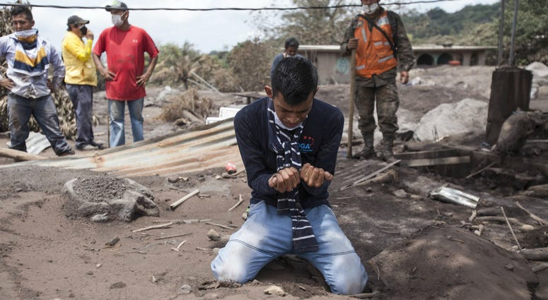 "Bryan Rivera cries after looking at the remains of his house, after his family went missing during the Volcan de Fuego or ""Volcano of Fire"" eruption, in San Miguel Los Lotes, Guatemala, Thursday, June 7, 2018."