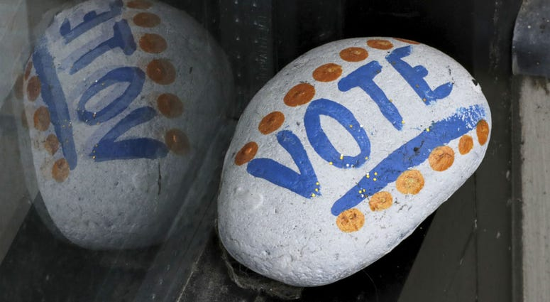"""In this March 22, 2019, file photo, a stone painted with the word """"VOTE"""" rests on the window sill of an art gallery in Peterborough, N.H."""