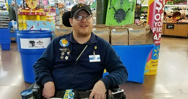 In this April 21, 2018 photo provided by Rachel Wasser, Walmart greeter John Combs works at a Walmart store in Vancouver, Wash.