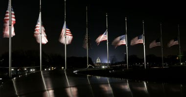 In this Dec. 30, 2006, file photo with the Capitol in the background, American flags fly at half-staff at the foot of the Washington Monument in Washington.